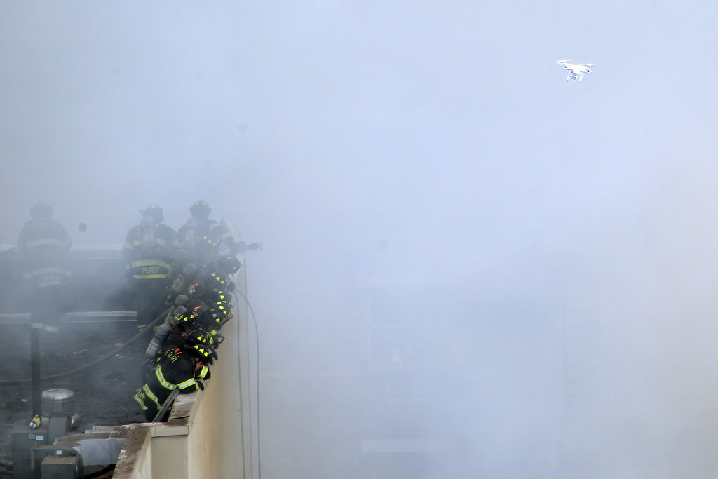 . Firefighters from the Fire Department of New York (FDNY) respond to a five-alarm fire and building collapse at 1646 Park Ave as a drone flies overheard in the Harlem neighborhood of Manhattan March 12, 2014 in New York City.   (Photo by Justin Heiman/Getty Images)