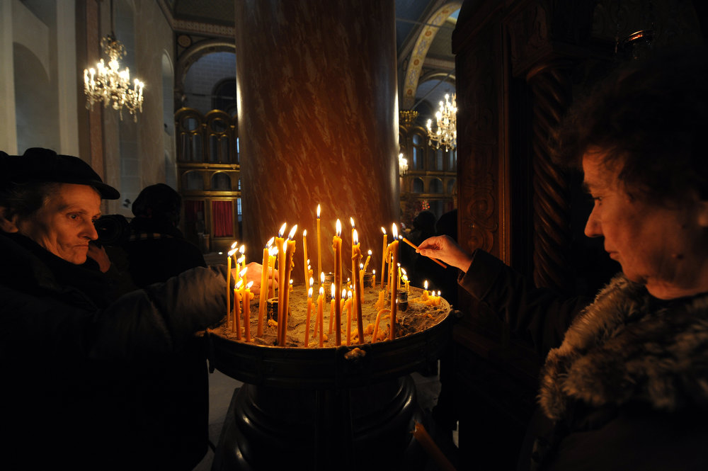 ". Bosnian Orthodox Serb light candles to commemorate passed souls of their relatives, during Christmas Mass at ""Congregational Church of The Mother of God\"" in Sarajevo, on January 7, 2013. Dominantly Orthodox Christians, Bosnian Serbs observe the old \""Julian\"" calendar differing from Catholic and secular, \""Gregorian\"" calendar, established in 16th century. AFP PHOTO ELVIS  BARUKCIC/AFP/Getty Images"