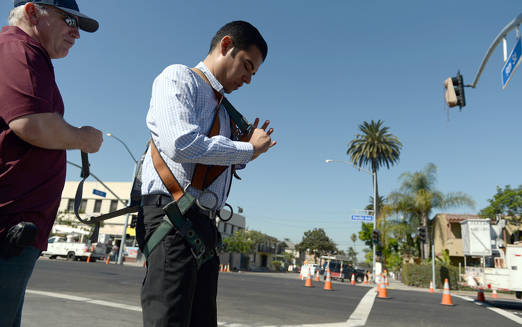 . Long Beach Vice Mayor Robert Garcia straps on a body harness as he prepares to unveil the new traffic signal at Pacific Avenue and Ninth Street at a brief ceremony in Long Beach, CA. Monday September 16, 2013.   (Photo by Thomas R. Cordova/ Daily Breeze)
