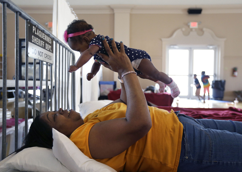 . Rhonda Etienne of Davant,La., holds her niece Nevaeh Etienne, three months, in an evacuation shelter in Belle Chasse, La., in anticipation of Tropical Storm Karen, Saturday, Oct. 5, 2013. The East Bank of Plaquemines Parish has been under a mandatory evacuation, which has been downgraded to a voluntary evacuation. (AP Photo/Gerald Herbert)