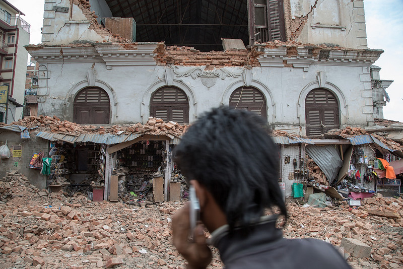 . A young man speaks on the phone in front of a collapsed building in the city center following an earthquake on April 25, 2015 in Kathmandu, Nepal. A major 7.8 earthquake hit Kathmandu mid-day on Saturday, and was followed by multiple aftershocks that triggered avalanches on Mt. Everest that buried mountain climbers in their base camps. Many houses, buildings and temples in the capital were destroyed during the earthquake, leaving hundreds dead or trapped under the debris as emergency rescue workers attempt to clear debris and find survivors.  (Photo by Omar Havana/Getty Images)