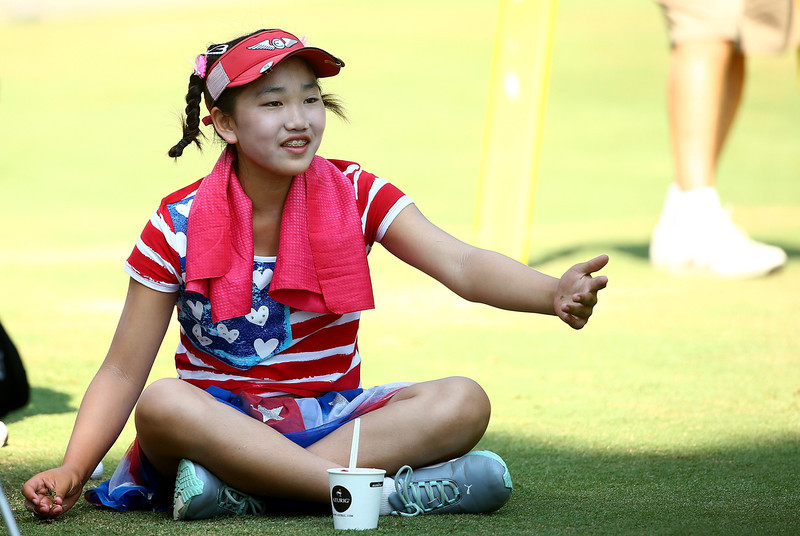 . Eleven-year old Amateur Lucy Li of the United States takes a break as she waits to hit on the third hole during the first round of the 69th U.S. Women\'s Open at Pinehurst Resort & Country Club, Course No. 2  on June 19, 2014 in Pinehurst, North Carolina.  (Photo by Streeter Lecka/Getty Images)