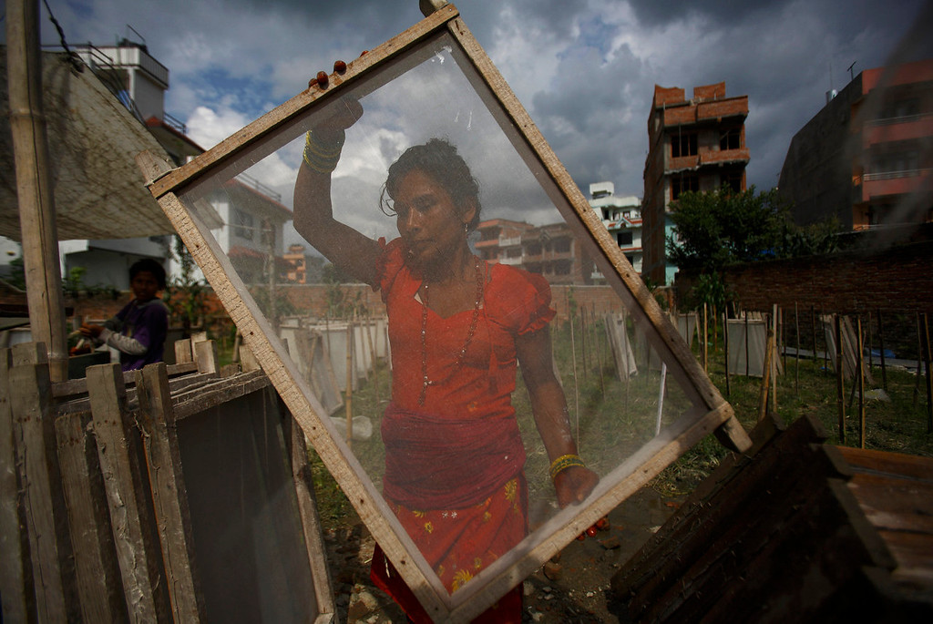 . Kumari Nepali, wife of Arjun Nepali, carries a frame used to make Handmade Nepali Lokta Paper as she prepares to makes one at a factory in Bhaktapur July 17, 2013. According to Arjun he earns 300 Nepalese rupees ($3.15) a day working at a factory from which he runs his house and sends his three sons to a government school. Lokta papers are made up of fibrous inner bark of Lokta bushes that are found above 5,000 m above sea level. According to factory owner Shyam Hari Kadel most of the papers that he produced are exported to countries like Germany and Britain.  REUTERS/Navesh Chitrakar