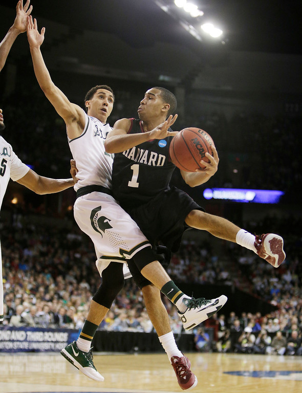 . Harvardís Siyani Chambers (1) passes around Michigan Stateís Travis Trice in the second half during the third-round game of the NCAA men\'s college basketball tournament in Spokane, Wash., Saturday, March 22, 2014. Michigan State won 80-73. (AP Photo/Young Kwak)