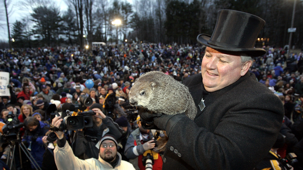 . Punxsutawney Phil, the weather predicting groundhog, is held by his handler Bill Deeley in front of an announced crowd of 14,000 who came to hear the prediction of six more weeks of winter in Punxsutawney, Pa. on Thursday, Feb. 2, 2006. (AP Photo/Keith Srakocic)