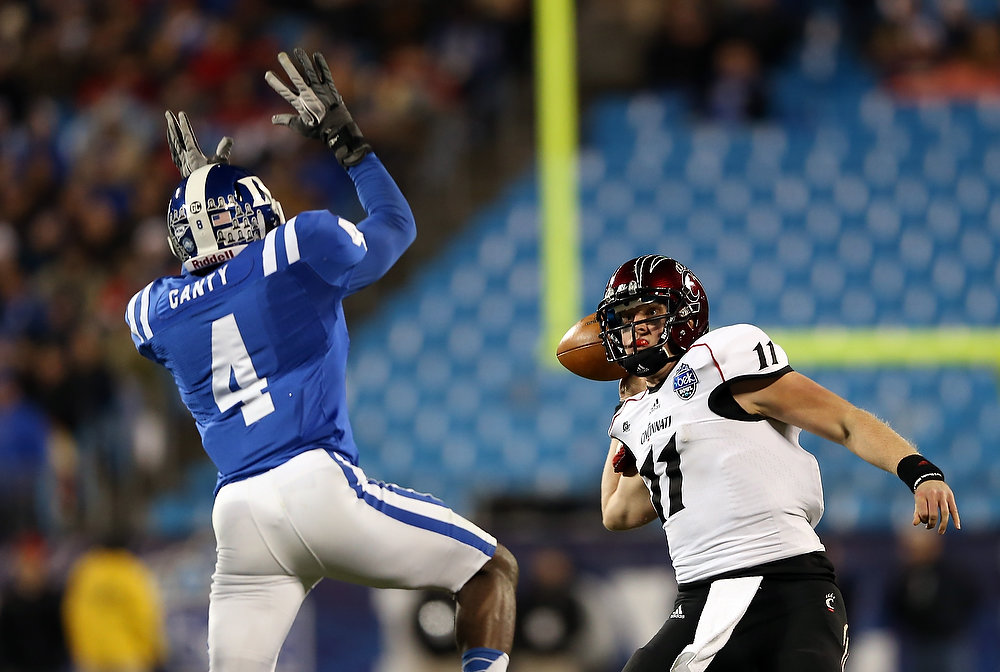Description of . Brendon Kay #11 of the Cincinnati Bearcats throws a pass over Walt Canty #4 of the Duke Blue Devils during their game at Bank of America Stadium on December 27, 2012 in Charlotte, North Carolina.  (Photo by Streeter Lecka/Getty Images)