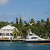 Large and luxury white home in the tropics with a large deep sea fishing boat in dock.
