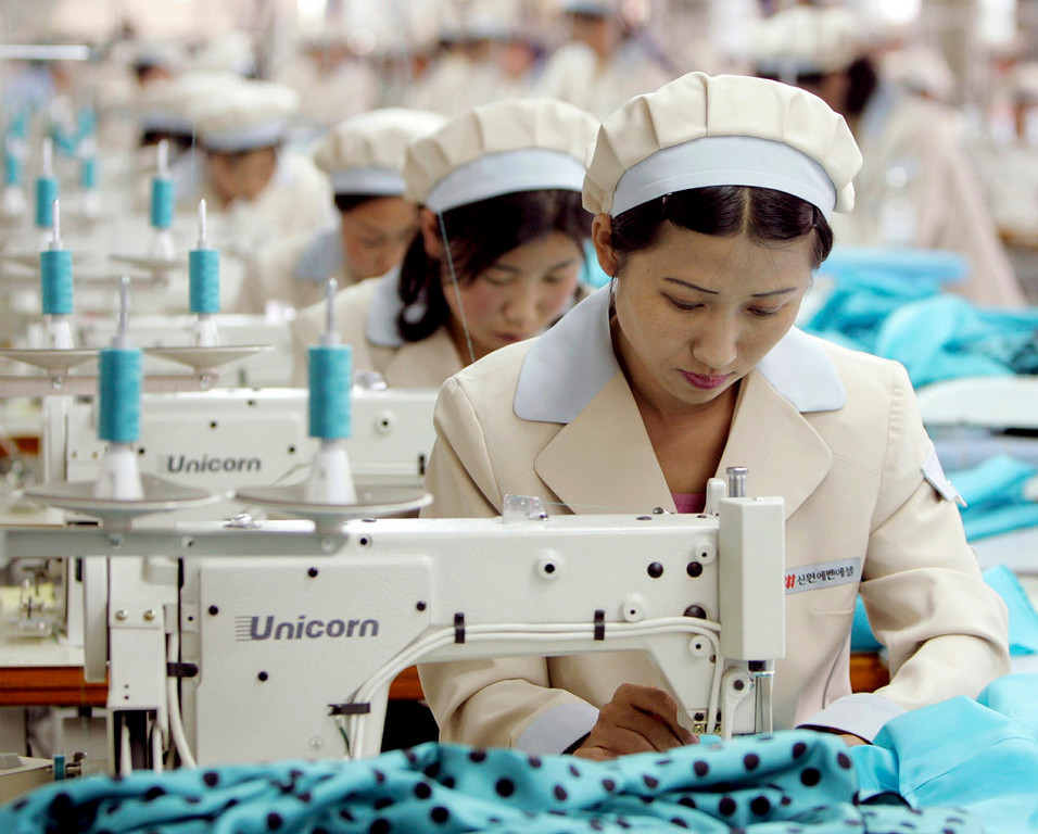 . North Korean workers work at a factory of South Korean apparel maker Shinwon company in the inter-Korean industrial park in Kaesong, north of the heavily fortified Demilitarized Zone that divides the Korean peninsula in this May 26, 2005 file photo. North Korea said on April 8, 2013 it would withdraw its workers from the Kaesong factory park jointly run with South Korea and temporarily suspend all operations there.   REUTERS/Lee Jae-won/Files