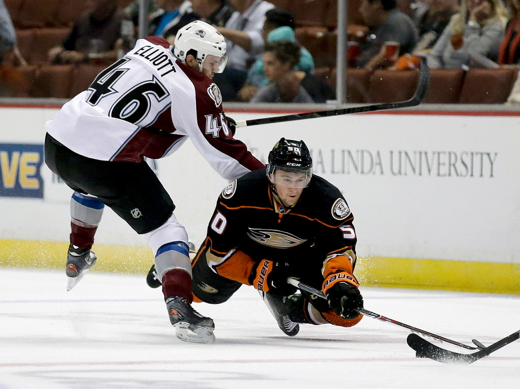 . Anaheim Ducks left wing Nicolas Kerdiles, right, dives for the puck as Colorado Avalanche defenseman Stefan Elliott looks on during the first period of an NHL hockey preseason game in Anaheim, Calif., Monday, Sept. 22, 2014. (AP Photo/Chris Carlson)