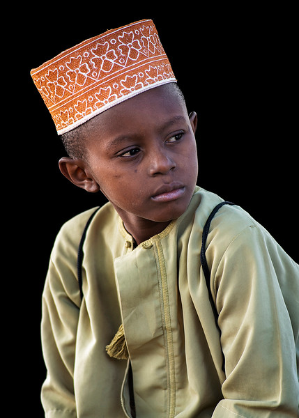 Little Muslim boy stopped for a picture on his way to school in the town of Pangani.   Pangani, Tanzania, 2019.