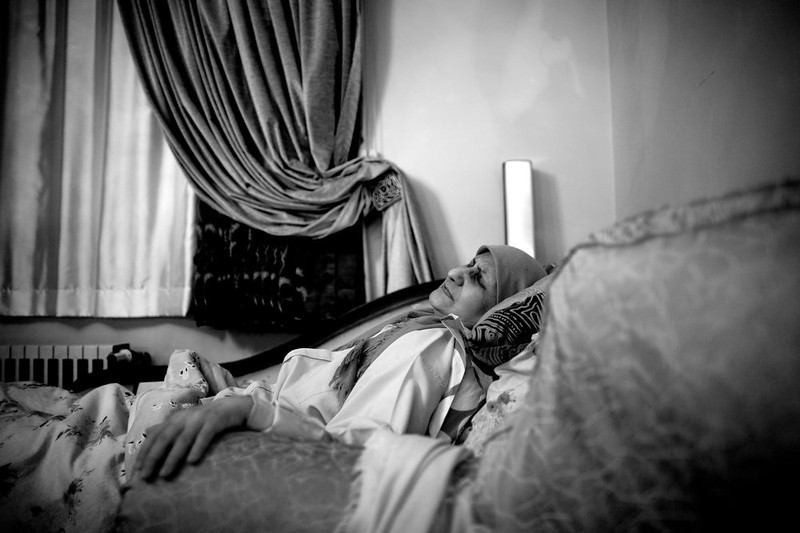. Iranian breast cancer patient Soheila Mehri suffers from pain as she lies in her bed in her house in Tehran on March 3, 2013.  AFP PHOTO/BEHROUZ MEHRI