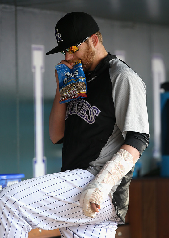 . Pitcher Brett Anderson #30 of the Colorado Rockies opens a bag of sunflower seeds in the dugout as the team faces the Philadelphia Phillies at Coors Field on April 20, 2014 in Denver, Colorado. Anderson is on the disabled list with a broken finger as the Philles defeated the Rockies 10-9.  (Photo by Doug Pensinger/Getty Images)