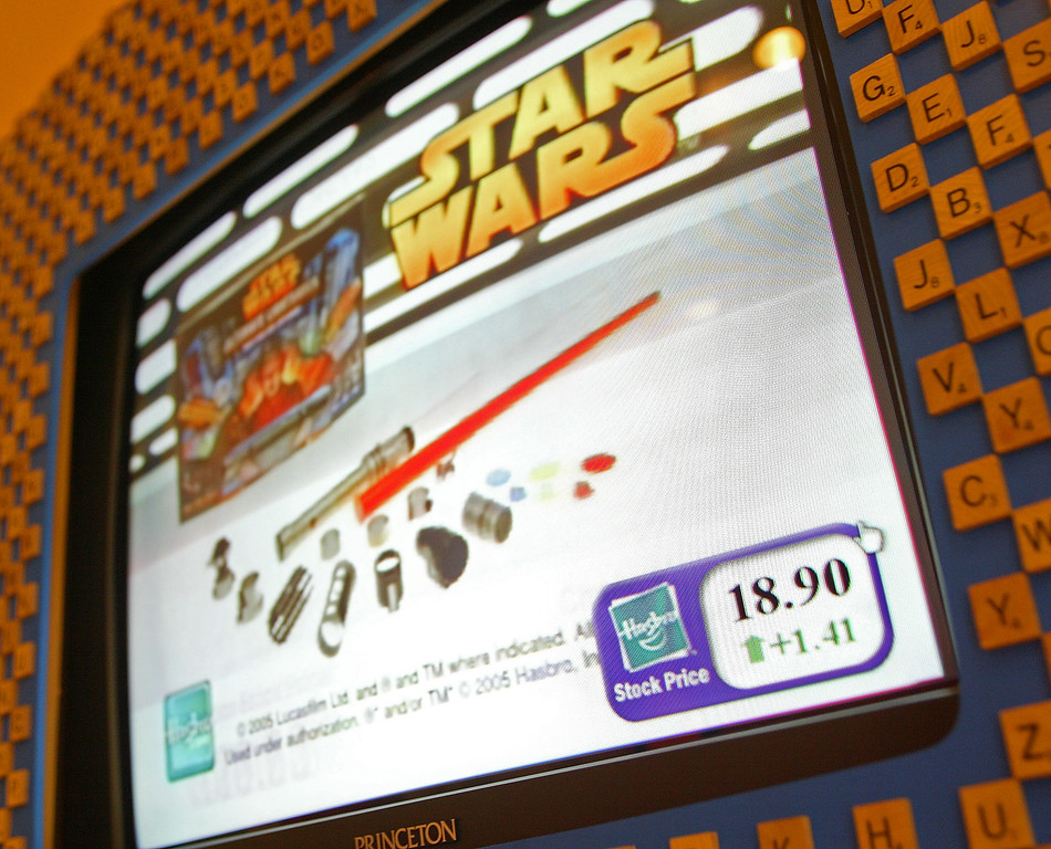 ". A television displaying Hasbro commercials in the lobby of Hasbro, Inc., in Pawtucket, R.I., shows the company\'s stock finished the day up +$1.41 at $18.90 a share, despite the declining revenue in ""Star Wars\"" product sales, Monday, July 24, 2006.  Due to an anticipated drop in \""Star Wars\"" product sales, Hasbro Inc., the nation\'s second-largest toy maker that earnings and revenue declined in the second quarter. (AP Photo/Stew Milne)"