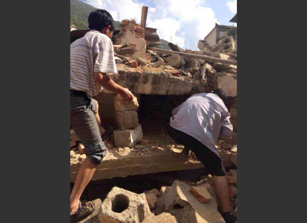 . In this photo taken by cellphone and released by China\'s Xinhua News Agency, men at rubbles of buildings look for survivors after an earthquake in Ludian County of Zhaotong City in southwest China\'s Yunnan Province Sunday, Aug. 3, 2014. A strong earthquake rattled southwest China on Sunday, knocking out communication and power lines and causing people to rush out of buildings, but there were no immediate reports of injuries. (AP Photo/Xinhua/Hu Chao)