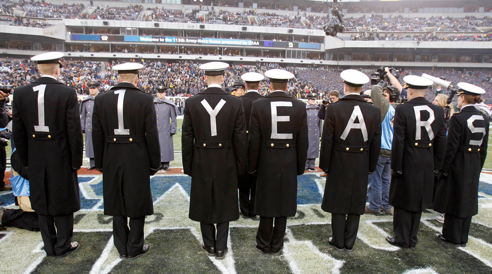 ". Midshipmen wear ""11 years\"" on their backs in reference to the Naval Academy\'s 11 game winning streak over the U.S. Military Academy before the start of the Army versus Navy NCAA football game in Philadelphia, Pennsylvania, December 8, 2012. REUTERS/Tim Shaffer"