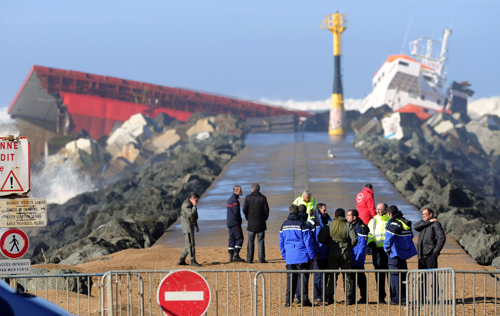 . Rescuers and officials walk next to a Spanish cargo ship which slammed into a dyke and split in two, injuring at least one sailor and raising concerns of a fuel leak, in Anglet, near the French port of Bayonne, on February 5, 2014. AFP PHOTO/GAIZKA IROZ/AFP/Getty Images