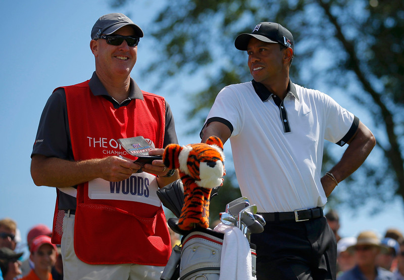 . Tiger Woods of the U.S.(R) speaks with his caddie Joe Lacava as he waits to tee off on the second hole during the first round of the British Open golf championship at Muirfield in Scotland July 18, 2013. REUTERS/Brian Snyder
