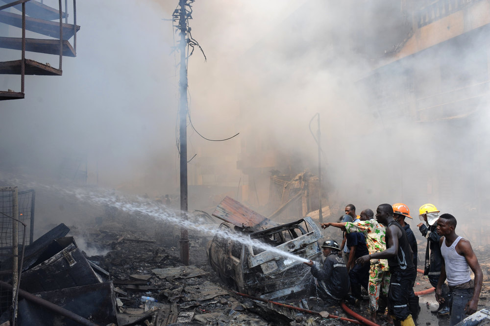 Description of . Firefighters try to put out a fire at the building following an explosion in Lagos on December 26, 2012. Fire ripped through a crowded neighborhood in Nigeria\'s largest city on Wednesday and wounded at least 30 people after a huge explosion rocked a building believed to be storing fireworks, officials said.  AFP PHOTO/PIUS UTOMI EKPEI/AFP/Getty Images