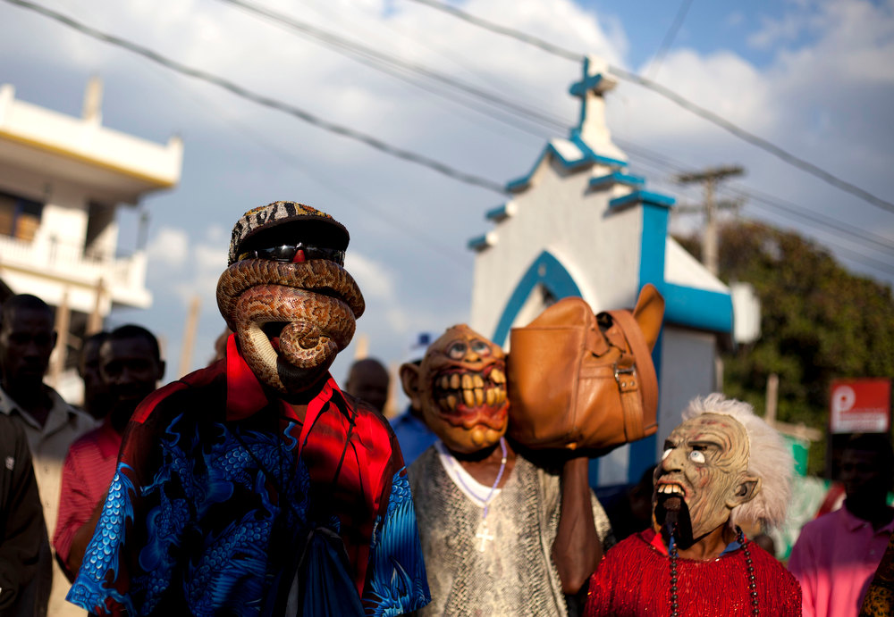 . In this Jan. 27, 2013 photo, snake handler Saintilus Resilus performs with a snake wrapped around his face as he and his assistants walk in the streets during pre-Lenten Carnival celebrations in Petionville, Haiti.  Haiti\'s snakes aren\'t venomous, but they have poisoned some relationships. Resilus\' wife left him in 1991. (AP Photo/Dieu Nalio Chery)
