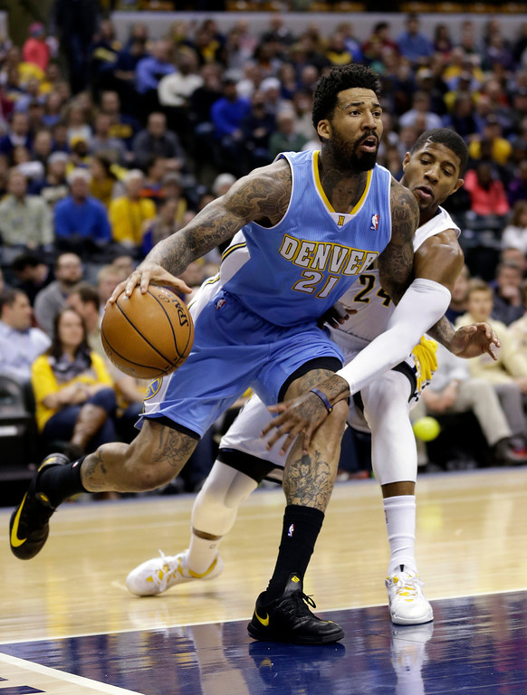 . Indiana Pacers forward Paul George, right, reaches around Denver Nuggets forward Wilson Chandler (21) as he drives the baseline in the first half of an NBA basketball game in Indianapolis, Monday, Feb. 10, 2014.  (AP Photo/Michael Conroy)