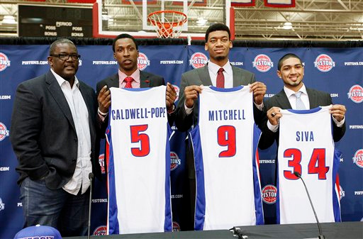 Description of . Detroit Pistons' President of Basketball Operations Joe Dumars, from left, stands with draft picks Kentavious Caldwell-Pope (5), Tony Mitchell (9) and Peyton Siva(34) while they hold their uniforms at the NBA basketball team's training facility in Auburn Hills, Mich., Friday, June 28, 2013. (AP Photo/Paul Sancya)