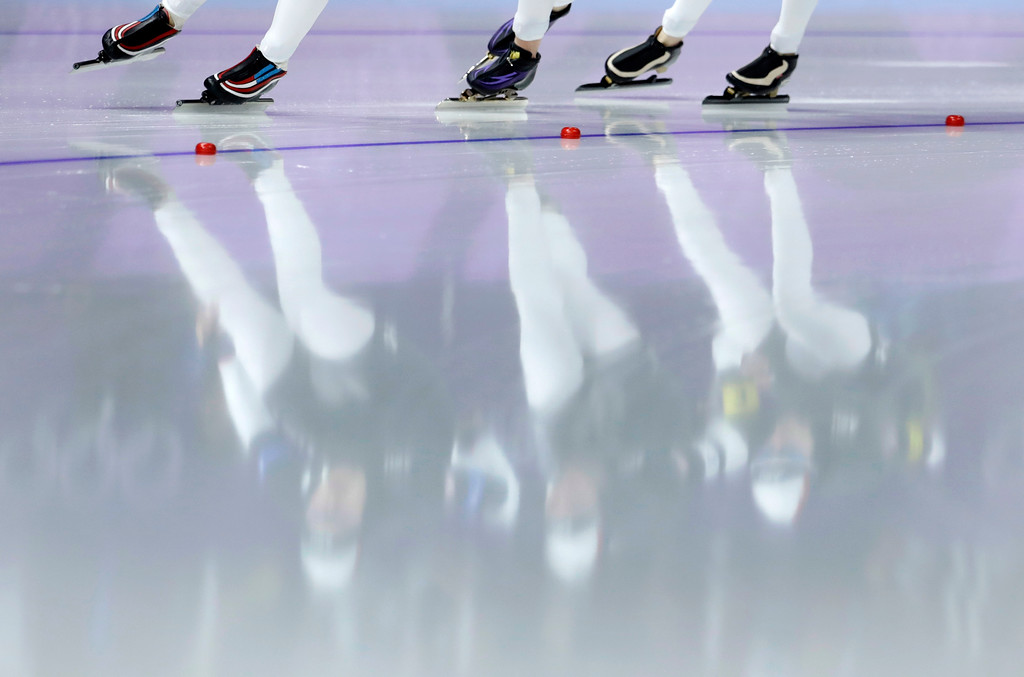 . Team U.S.A. with Heather Bergsma, Mia Manganello, and Carlijn Schoutens is reflected in the ice during the women\'s team pursuit semifinal speedskating race at the Gangneung Oval at the 2018 Winter Olympics in Gangneung, South Korea, Wednesday, Feb. 21, 2018. (AP Photo/Petr David Josek)