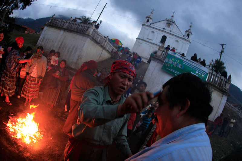 ". A man is ""cleansed\"" with candles next to a sacred fire during the pre-Hispanic mass of \""Segunda Conexion\"" (Second Connection) to commemorate the 13th bak\'tun, an epoch lasting roughly 400 years, outside the Chi Ixim church in Tactic, Alta Verapaz region, Guatemala, December 20, 2012. On December 21, an era closes in the Maya Long Count calendar, an event that has been likened by different groups to the end of days, the start of a new, more spiritual age or a good reason to hang out at old Maya temples across Mexico and Central America. The Chi Ixim church is a sacred Mayan site. REUTERS/Jorge Dan Lopez"