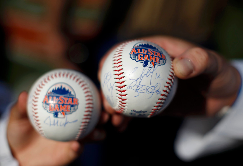 . Fans hold autographed baseballs ahead of Major League Baseball\'s All-Star Game in New York, July 16 2013. REUTERS/Mike Segar