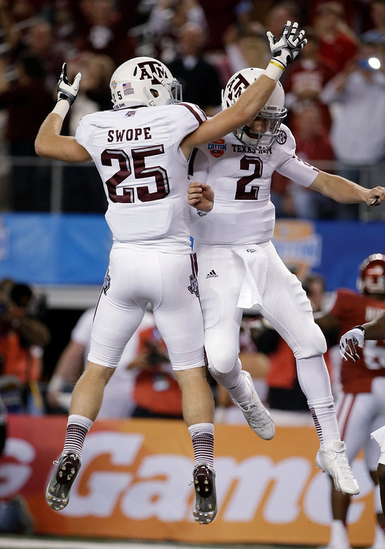 . Texas A&M\'s Ryan Swope (25) and Johnny Manziel (2) celebrate a touchdown run by Manziel against Oklahoma in the first half of the Cotton Bowl NCAA college football game Friday, Jan. 4, 2013, in Arlington, Texas. (AP Photo/Tony Gutierrez)