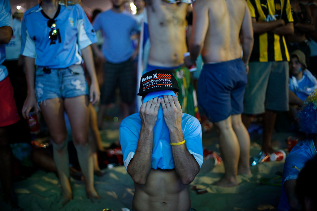 . An Uruguay soccer fan covers his face as he cries after his team lost  their first game of the 2014 Soccer World Cup against Costa Rica, inside the FIFA Fan Fest area on Copacabana beach in Rio de Janeiro, Brazil, Saturday, June 14, 2014. Costa Rica upset Uruguay 3-1 in the first game of group D. (AP Photo/Silvia Izquierdo)