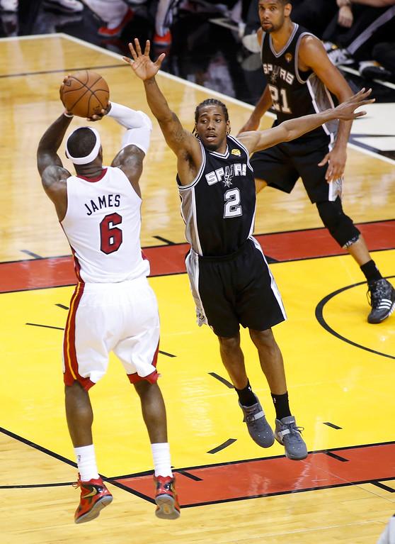 . Miami Heat\'s LeBron James (6) shoots a basket over San Antonio Spurs\' Kawhi Leonard near the end of Game 7 of their NBA Finals basketball playoff in Miami, Florida June 20, 2013. REUTERS/Joe Skipper
