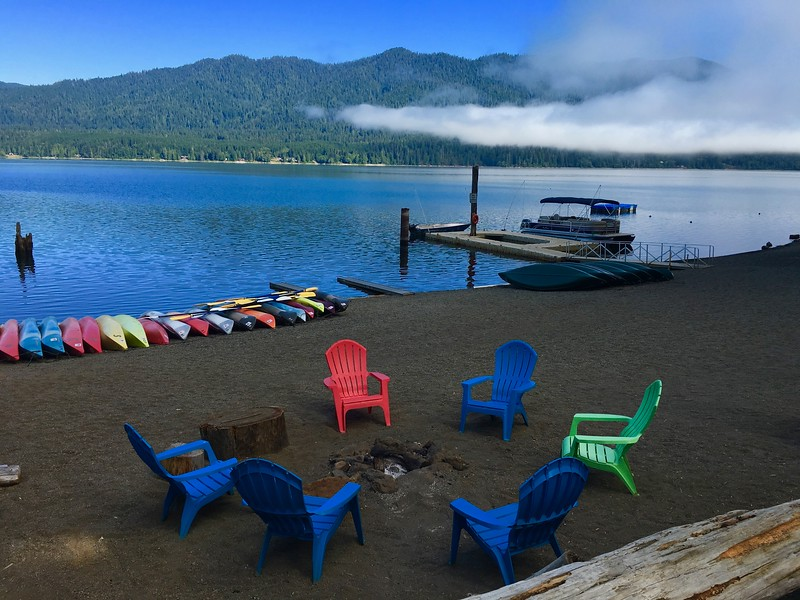 shore of beach with colorful chairs and kayaks