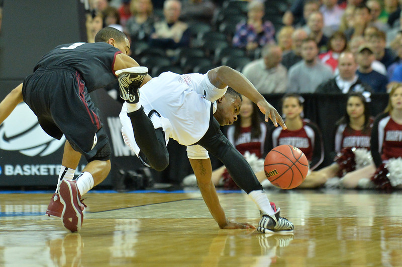March 20, 2014: Cincinnati Bearcats guard Ge'Lawn Guyn (14) tries to maintain his balance during a second round game of the NCAA Division I Men's Basketball Championship between the 5-seed Cincinnati Bearcats and the 12-seed Harvard Crimson at Spokane Arena in Spokane, Wash. Harvard defeated Cincinnati 61-57.