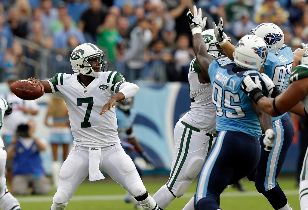 . New York Jets quarterback Geno Smith (7) passes as Tennessee Titans defenders Kamerion Wimbley (95) and Karl Klug (97) pressure him in the first quarter of an NFL football game on Sunday, Sept. 29, 2013, in Nashville, Tenn. (AP Photo/Wade Payne)