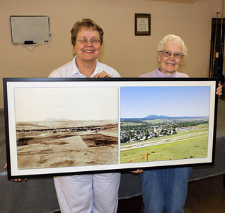 """Spearfish Area Historical Society member Dorothy Pawlowski (at right) presents a framed """"Then and Now"""" photograph of Spearfish to Senior Citizen Center director Lovina Dodson.  The wonderful contrasting photos were assembled by Horsted, who donated it to the society. In October, the society conducted a raffle for the photographs, and Dorothy was the winner!  After winning the photo, Dorothy chose to donate it to the Spearfish Senior Citizen's Center, where the society has held its meetings for many years.   Our congratulations -- and thanks -- to Dorothy.  And thanks, too, to Paul Horsted for his great work and generosity!"""