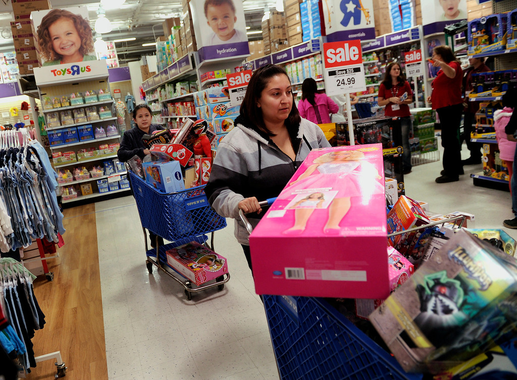 . Jennifer Martinez, front, and her sister Geena Gallegos, behind her, each filled a cart with toys at the Toys R Us store on County Line Road in Arapahoe CountyThursday night, November 28, 2013. Many metro area stores got a jump on Black Friday by opening Thanksgiving night. Photo By Karl Gehring/The Denver Post