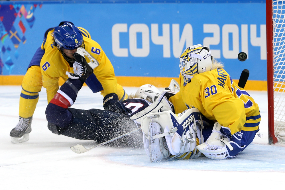. SOCHI, RUSSIA - FEBRUARY 17:  Jocelyne Lamoureux #17 of the United States gets taken down while trying to shoot against Lina Backlin #6 and Kim Martin Hasson #30 of Sweden in the third period during the Women\'s Ice Hockey Playoffs Semifinal game on day ten of the Sochi 2014 Winter Olympics at Shayba Arena on February 17, 2014 in Sochi, Russia.  (Photo by Bruce Bennett/Getty Images)
