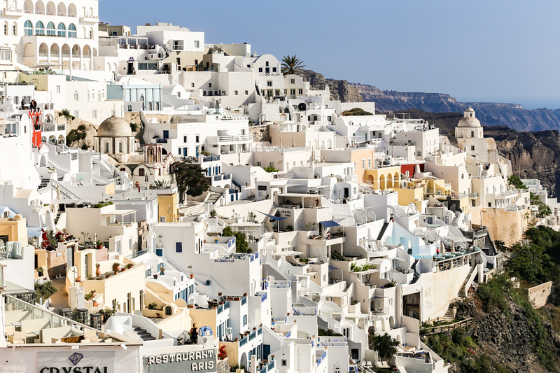 White hillside buildings on Fira, part of a Greek Islands cruise itinerary