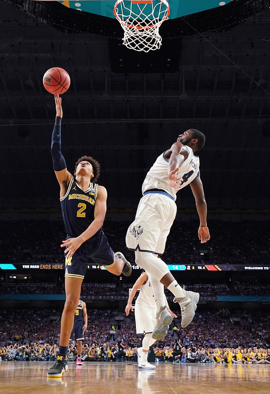 . Michigan\'s Jordan Poole (2) shoots against Villanova\'s Eric Paschall (4) during the first half in the championship game of the Final Four NCAA college basketball tournament, Monday, April 2, 2018, in San Antonio. (AP Photo/Chris Steppig, NCAA Photos Pool)