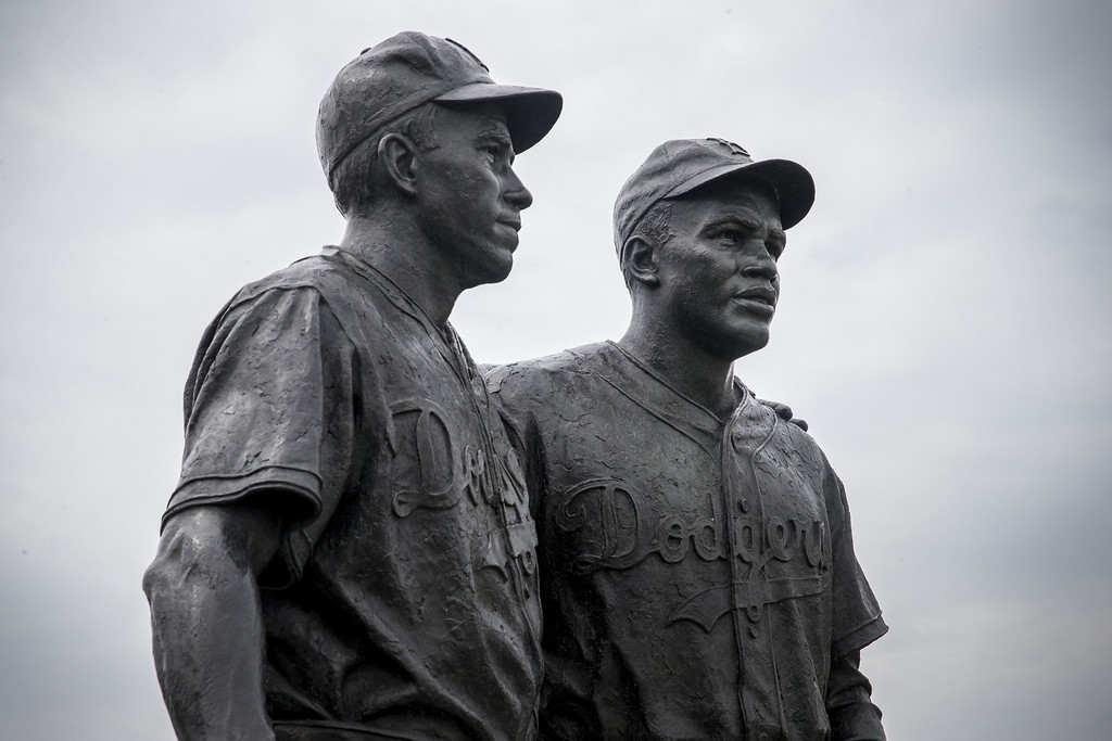. A statue of Pee Wee Reese (L) and Jackie Robinson, stands after being cleaned of racist graffiti on August 9, 2013 in the Coney Island neighborhood of the Brooklyn borough of New York City. Robinson broke the color barrier for Major League Baseball in 1947 when he joined the Brooklyn Dodgers and Reese was a teammate and supporter. The statue was unveiled in 2005.  (Photo by Andrew Burton/Getty Images)