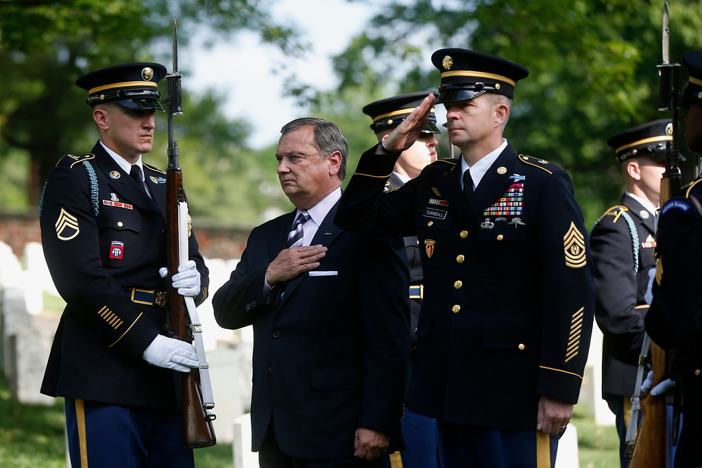 ". Jack Lechner, Deputy Superintendent of Arlington National Cemetery, center, and Army Command Sgt. David O. Turnbull, right, stand during the playing of ""Taps\"" after a wreath was laid at the gravesite of Army Pvt. William Christman, who was the first military burial at the cemetery, marking the beginning of commemorations of the 150th anniversary of Arlington National Cemetery in Arlington, Va., Tuesday, May 13, 2014. (AP Photo)"