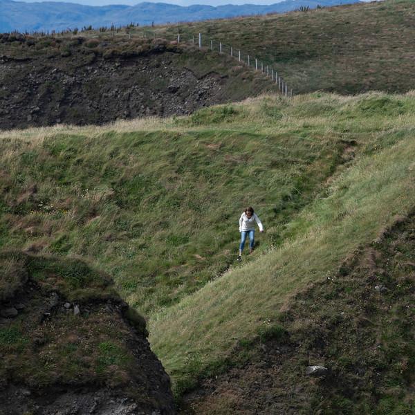 Woman climbing the hills of Mullaghmore Peninsula, County Sligo, Ireland