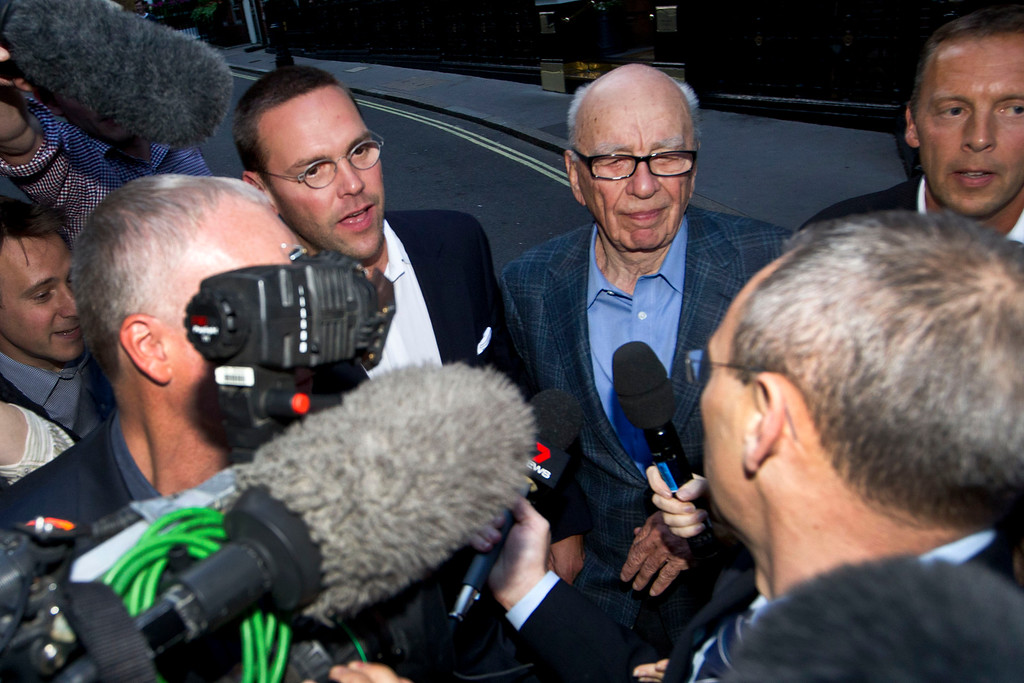 . Chairman of News Corporation Rupert Murdoch, center right, and his son James Murdoch, center left, chief executive of News Corporation Europe and Asia face the media as they arrive at his residence in central London, Sunday, July 10, 2011.  (AP Photo/Sang Tan)