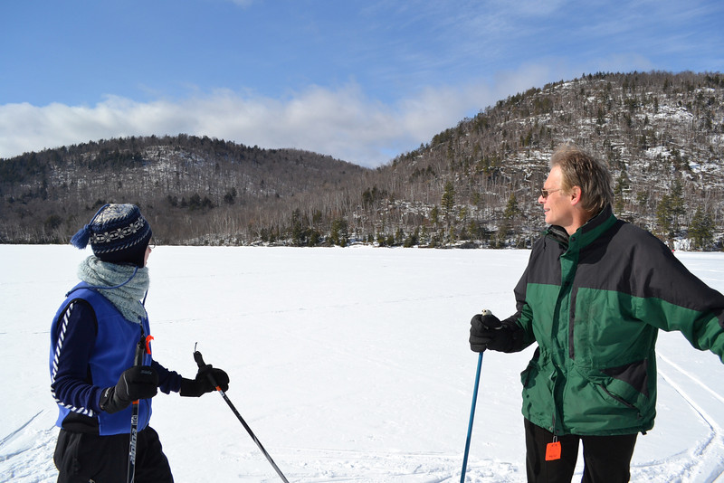 Elise and Steve ponder the deeper meanings of snow, skiing, and how freezing cold it is since there's no protection from the wind on the lake.
