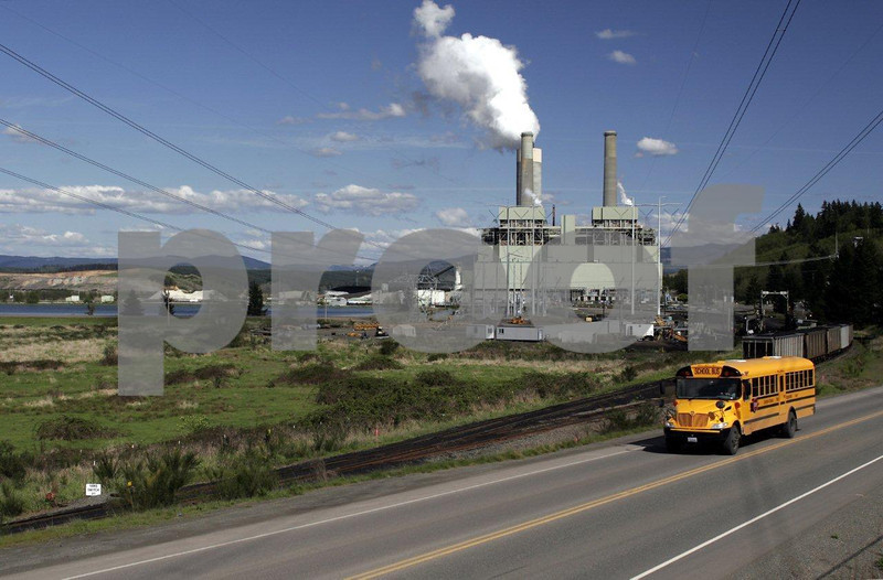 A school bus passes by the Centralia Steam Electrtic Plant fed by an open pit coal mine.
