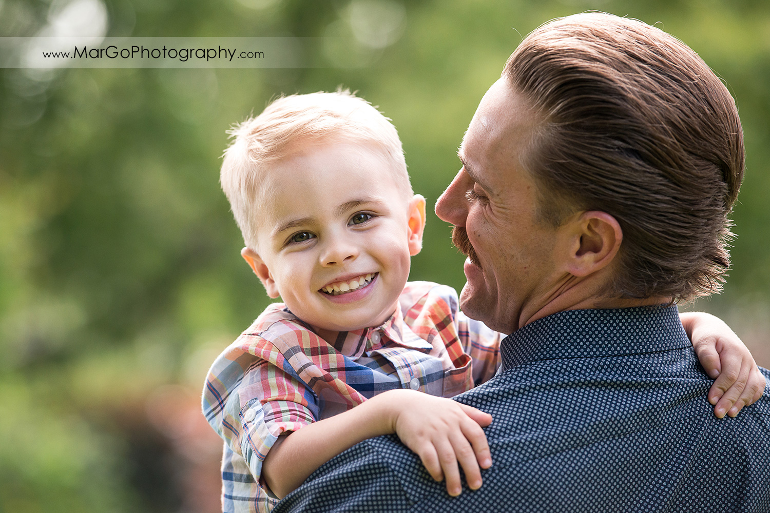 portrait of smiling boy in his dad's arms in Shinn Historical Park and Arboretum in Fremont