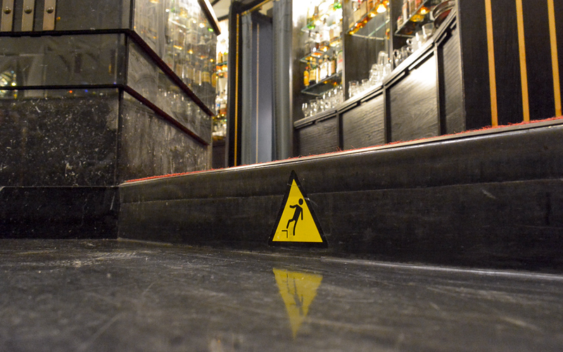 This photo shows the step leading up to the bar of the American Bar in the Municipal House in Prague. The yellow warning triangle is for the bartender. The shiny objects in the background are liquor bottles. I don't think of Elliott drinks much but I imagine this scene would be both interesting and confusing.
