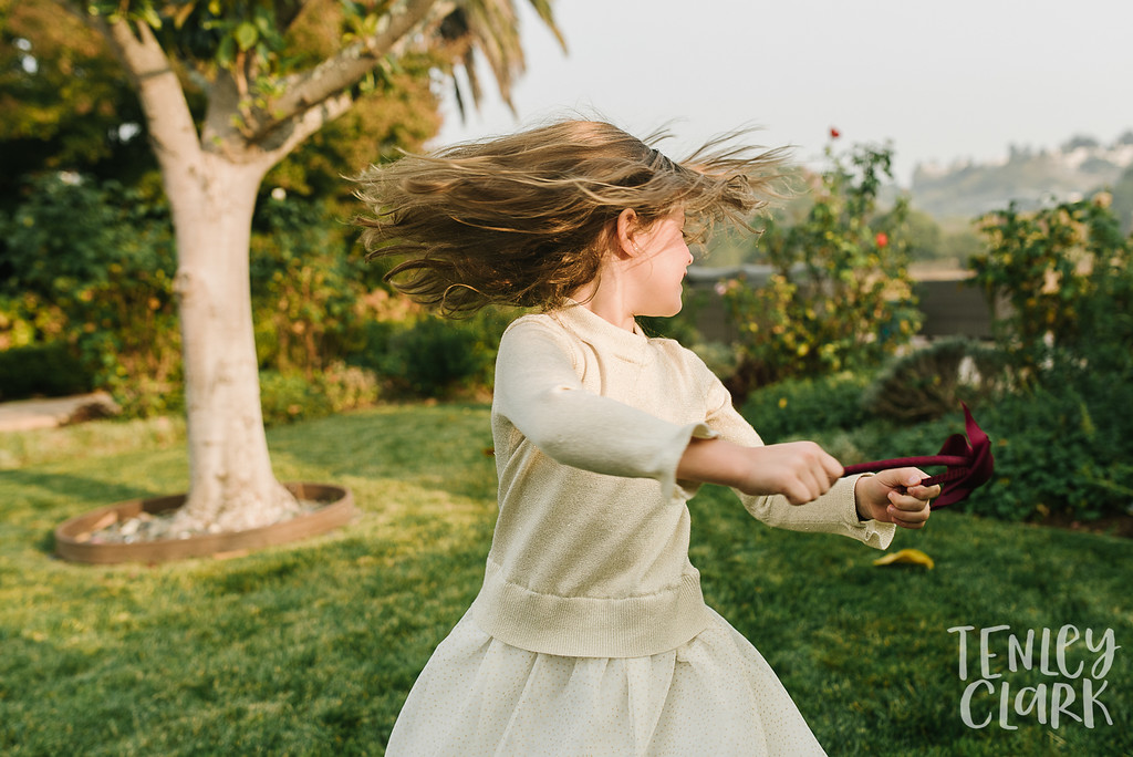 Little girl flipping her hair in backyard. Lifestyle in-home family photoshoot in Marin, CA by Tenley Clark Photography.