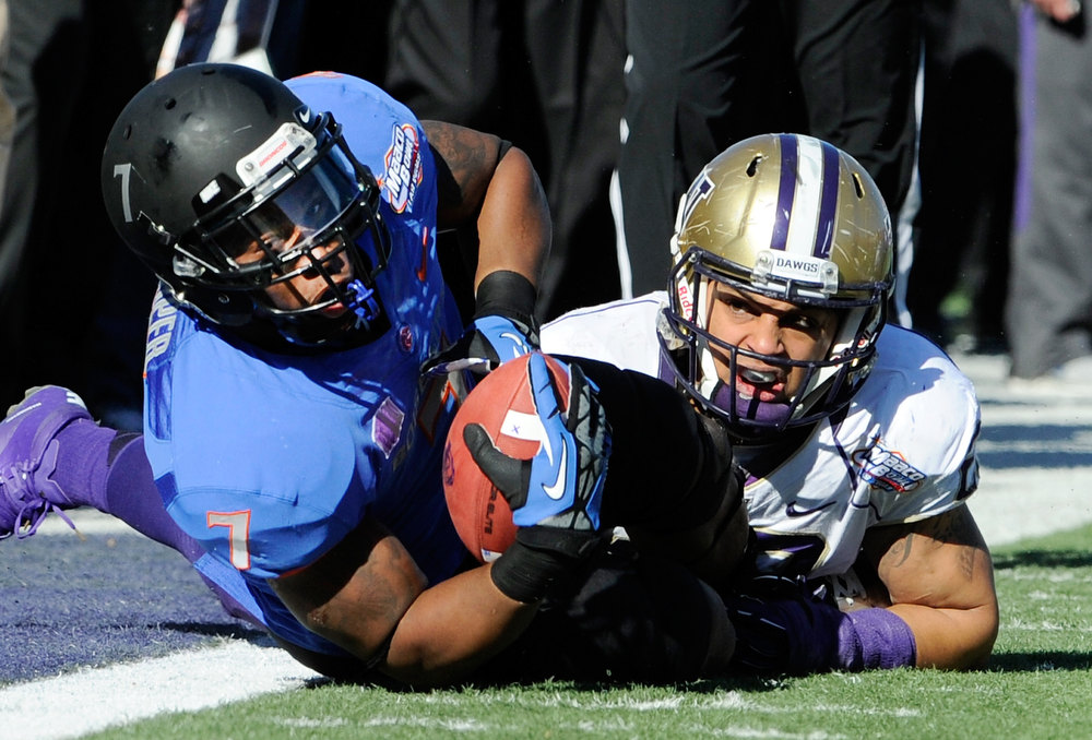 Description of . Boise State running back D. J. Harper hangs onto the ball after making a sideline reception with Washington's John Glenn defending during first half of the MAACO Bowl NCAA college football game on Saturday, Dec. 22, 2012, in Las Vegas. (AP Photo/David Becker)