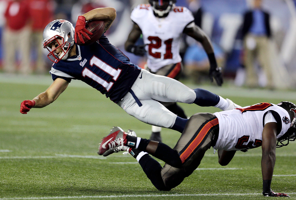 . Tampa Bay Buccaneers safety Keith Tandy, right, upends New England Patriots wide receiver Julian Edelman (11) after a catch in the second quarter of an NFL preseason football game Friday, Aug. 16, 2013, in Foxborough, Mass. (AP Photo/Charles Krupa)